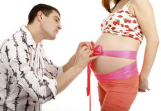 Man making a bow on a belly of pregnant woman Stock Photo