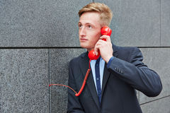 Man making call with red phone on wall Royalty Free Stock Photo