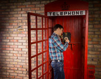Man making a call in a red telephone booth. Man standing making a call in a red British telephone booth with a vintage dial-up instrument Royalty Free Stock Photo