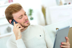 Man making call whilst using tablet computer Royalty Free Stock Photo