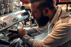 A man is making coffee in a professional coffee machine. Bearded male is making coffee in a professional coffee machine Stock Photo