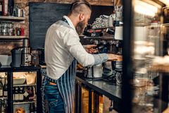 A man is making coffee in a professional coffee machine. Bearded male is making coffee in a professional coffee machine Stock Image