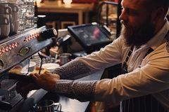 A man is making coffee in a professional coffee machine. Bearded male is making coffee in a professional coffee machine Royalty Free Stock Images