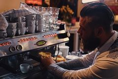 A man is making coffee in a professional coffee machine. Bearded male is making coffee in a professional coffee machine Royalty Free Stock Image