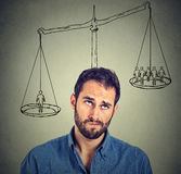 Man making a decision with scale above head and people on a balance. Power, opinion, self importance concept. Human face expression, emotions Stock Photo