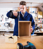 Man making drawer at workshop. Young positive joiner using drilling machine to make drawer at workshop Royalty Free Stock Photos