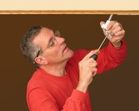 Man making electrical connection. To install track lighting Stock Photography
