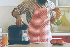 Man making espresso with coffee machine while breakfast Stock Image