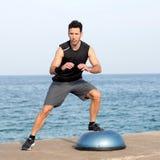 Man making exercise on balance platform Stock Photo
