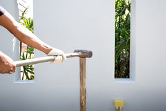 Man making fence with sledgehammer on the wood. In white background Stock Images