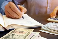Man is making financial calculations in the notepad. Bookkeeping. Royalty Free Stock Image