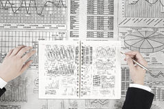 Man making financial notes. Businessman hands writing with pen infographs on paper Royalty Free Stock Photography