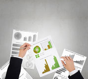 Man making financial notes. Businessman hands writing with pen infographs on paper Stock Image