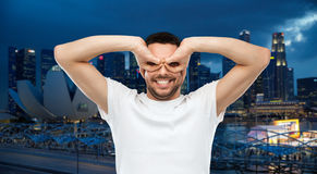 Man making finger glasses over city background Royalty Free Stock Image