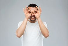 Man making finger glasses over gray background Royalty Free Stock Photo