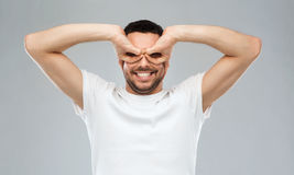 Man making finger glasses over gray background Royalty Free Stock Image