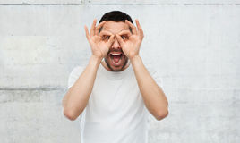 Man making finger glasses over gray background Royalty Free Stock Photos