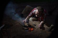 Man making firecamp outdoors at night. Royalty Free Stock Photo