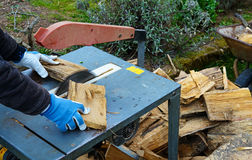 Man making firewood with buzz saw. In the garden Royalty Free Stock Photography