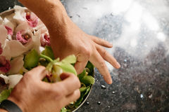 Man making flowers arrangment with green and white orhids. Man making flowers arrangment orchids Stock Photo