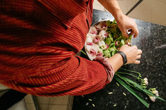 Man making flowers arrangment with green and white orhids. Man making flowers arrangment orchids Stock Images