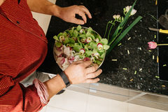 Man making flowers arrangment with green and white orhids. Man making flowers arrangment orchids Royalty Free Stock Photography