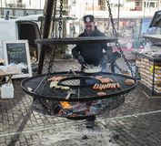 Man making food on the bbq. Dordrecht,Holland,16-12-2017, man making food on the bbq during the christmas market in Dordrecht, dordrecht has the biggest market Stock Photos