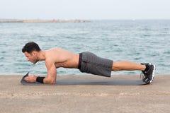 Man making forearm plank. Forearm plank exercise outside close to the beach Stock Photos
