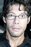 Man making funny face at camera. Young man with glasses making funny face at camera Stock Photo