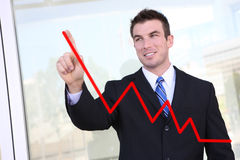 Man Making Graph Chart. Handsome  business man drawing a graph on a glass window at office - focus is on man Stock Images
