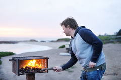 Man making grill near ocean Royalty Free Stock Photography