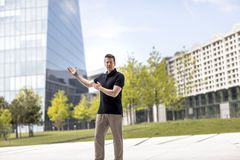 Man Making Hand Gestures in Front of Glass Building. A man making demonstrative hand gestures while standing in front of modern glass building Stock Photos