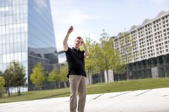 Man Making Hand Gestures in Front of Glass Building. A man making hand gestures while standing in front of modern glass building Royalty Free Stock Photography