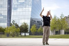Man Making Hand Gestures in Front of Glass Building. A man making hand gestures while standing in front of modern glass building Stock Photos