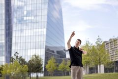 Man Making Hand Gestures in Front of Glass Building. A man making hand gestures while standing in front of modern glass building Stock Photography