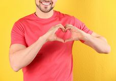 Man making heart with his hands on color background stock photo