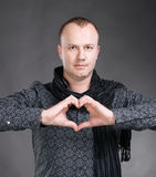 Man making heart sign. Young handsome man making heart sign on a gray background royalty free stock images