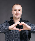 Man making heart sign. Young handsome man making heart sign on a gray background royalty free stock image