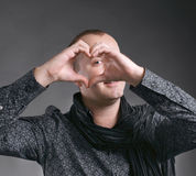 Man making heart sign. Young handsome man making heart sign on a gray background stock photo