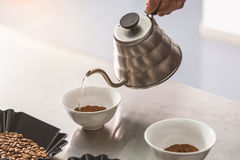 Man making invigorating dark drink. Person is adding water to ground roasted coffee beans. Utensils are on metal table. Close up of hand Royalty Free Stock Photos