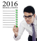 Man making a list of business resolutions for 2016. Portrait of young businessman writing a list of resolutions for 2016 on the whiteboard Royalty Free Stock Photo