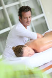 Man making a massage to a woman in a spa center. Masseur in spa institute doing massage to woman Royalty Free Stock Images