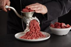 Man making minced meat with manual grinder. Man in black uniform making minced meat of beef or pork with old metal manual grinder. Pieces of fresh red meat for stock photography