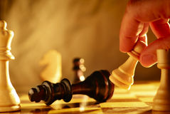 Man making a move in a game of chess. Knocking over a chess piece with a pawn that he is holding in his hand, close up view of the chess board Stock Photography