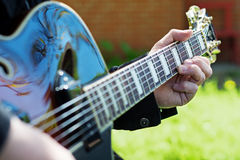 Man making music by playing guitar, detail with selected focus o Stock Image