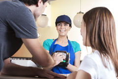 Man Making NFC Payment While Standing With Daughter And Waitress Stock Image