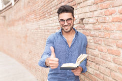 Man making the ok sign while reading a book Stock Image