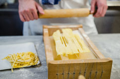 Man making pasta alla chitarra. Male cook preparing pasta with a chitarra and a rolling pin Royalty Free Stock Images