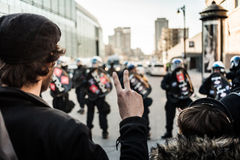 Man making a Peace sign in front of cops Stock Photos