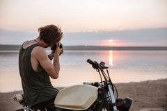 Man making photo with camera while sitting on his motocycle Stock Photo